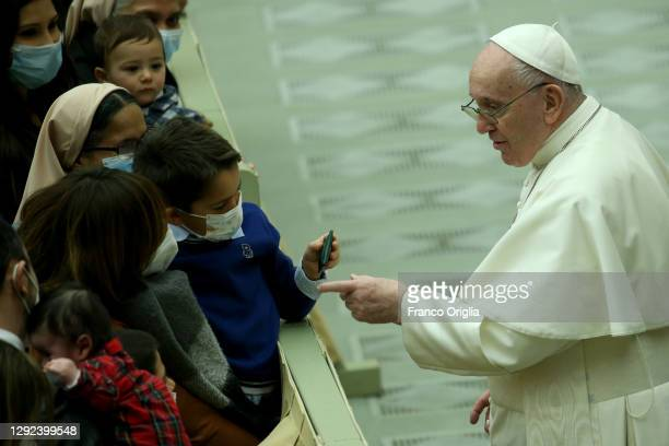 Pope Francis greets a child during an audience with Vatican employees for Christmas greetings at the Paul VI Hall on December 21, 2020 in Vatican...
