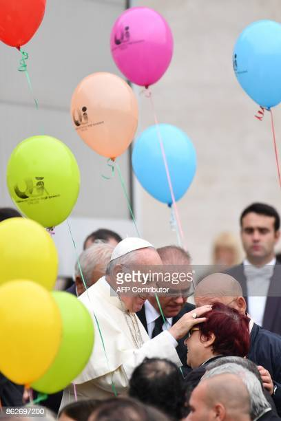 Pope Francis greets a group of partially sighted and blind people during his weekly general audience at St Peter's square on October 18 in Vatican /...