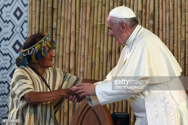 Pope Francis greets a representative of indigenous communities of the Amazon basin from Peru Brazil and Bolivia during a meeting in the Peruvian city...