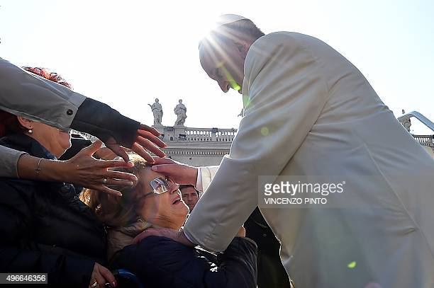 Pope Francis greets a woman seated on a wheelchair during his weekly general audience at St Peter's square on November 11 2015 at the Vatican AFP...