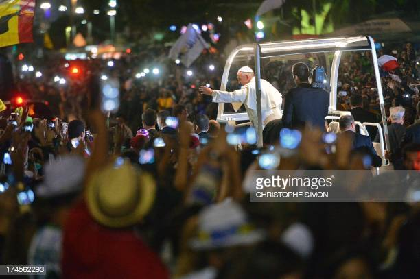 Pope Francis greets faithfuls standing along the beachfront in Rio de Janeiro on his way for a prayer vigil with hundreds of thousands of young...