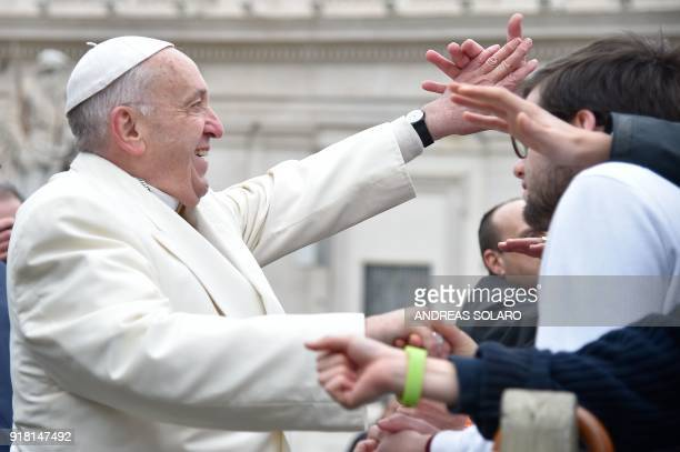 Pope Francis greets people at the end of his weekly general audience at St Peter's Square at the Vatican on February 14 2018 / AFP PHOTO / Andreas...