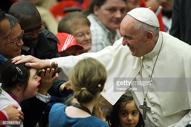 Pope Francis greets people during an audience for the people In precarious situations at the Paul VI Hall on November 11 2016 in Rome Italy After...