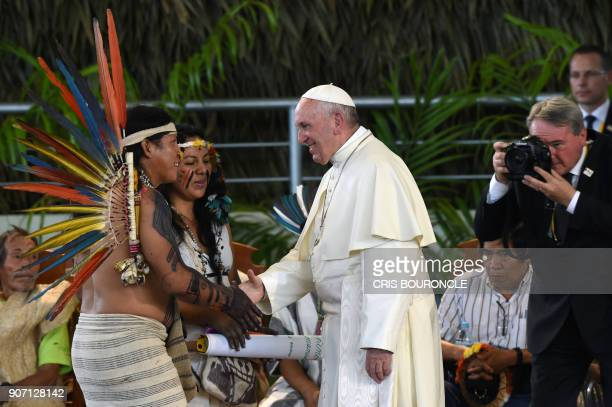Pope Francis greets representatives of indigenous communities of the Amazon basin from Peru Brazil and Bolivia during a meeting in the Peruvian city...
