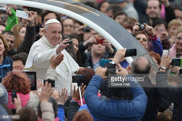 Pope Francis greets the crowd as he arrives for his weekly general audience at St Peter's square on February 3 2016 at the Vatican AFP PHOTO /...