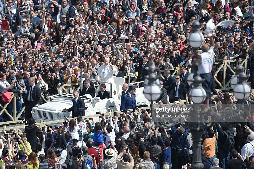 Pope Francis greets the crowd from the popemobile as a man has climbed on a streetlight to deploy a banner and protest against its dismissal after the Easter Sunday mass on March 27, 2016 at St Peter's square in Vatican. Christians around the world are marking the Holy Week, commemorating the crucifixion of Jesus Christ, leading up to his resurrection on Easter.