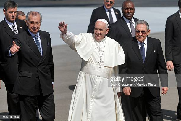 Pope Francis greets the press as he walks on the tarmac next to Cuba's president Raul Castro upon his arrival in Cuba, on February 12 in Havana,...