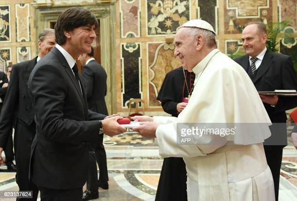 Pope Francis hands over a gift to Germany's football national team head coach Joachim Loew during a private audience with the team on November 14...