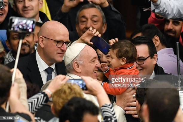 Pope Francis holds a child as he arrives for his weekly general audience at the Paul VI audience hall on December 13 2017 at the Vatican / AFP PHOTO...