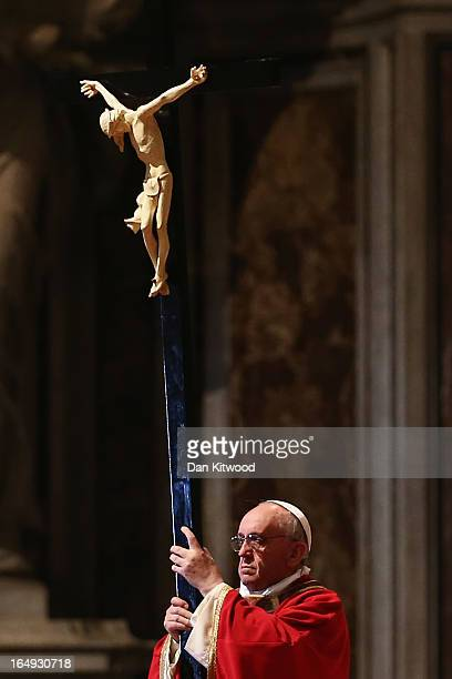 Pope Francis holds a crucifix aloft as he presides over a Papal Mass with the Celebration of the Lord's Passion inside St Peter's Basilica on March...