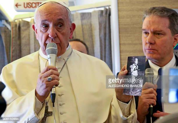 TOPSHOT Pope Francis holds a picture by US photographer Joseph Roger ODonnell depicting a Nagasaki victim as he speaks to journalists aboard the...