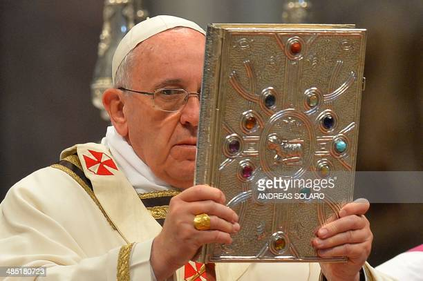 Pope Francis holds aloft the book of the gospels during a Chrism mass for Maundy Thursday on April 17 2014 at St Peter's Basilica in Vatican The...
