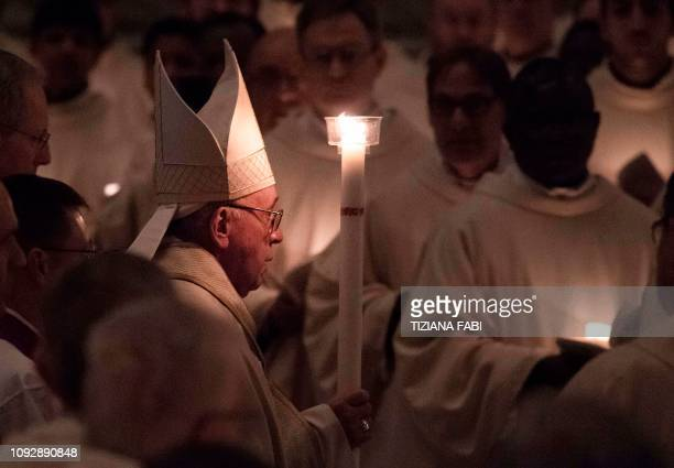 Pope Francis holds an altar candle as he arrives in the dark to celebrate a holy mass as part of the 23rd World Day for Consecrated Life on February...