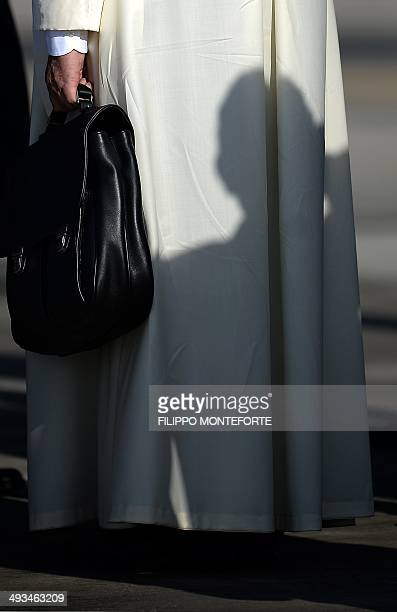 Pope Francis holds his bag under the stairs leading to the plane as he leaves to his trip to the holy land on May 24 2014 Pope Francis arrives in...
