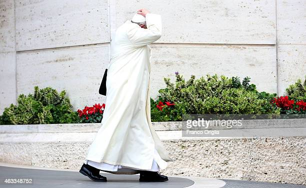 Pope Francis holds his biretta cup as he leaves the Synod Hall at the end of the Extraordinary Consistory for the creation of new cardinals on...