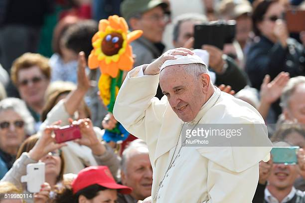 Pope Francis holds his skullcap as he waves to the faithfull upon his arrival for his special Jubilee Audience on Saint Peter's Square in the Vatican...