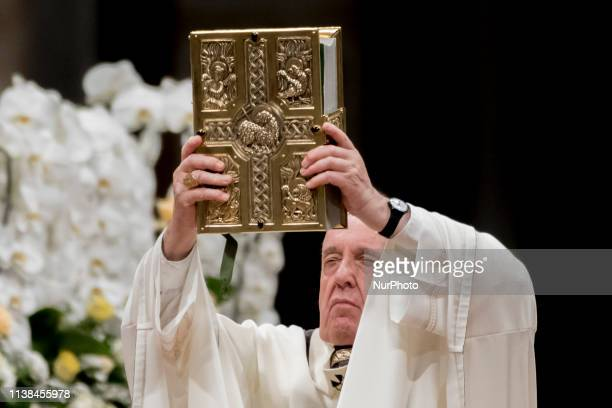 Pope Francis holds the Book of Gospels as he presides over the Easter Vigil on April 20 2019 at St Peter's Basilica in the Vatican Christians around...