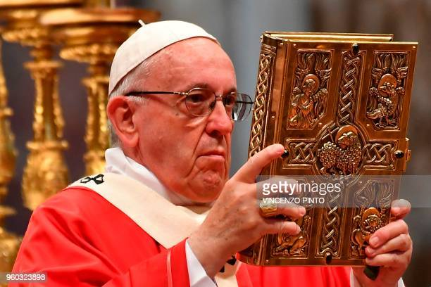 Pope Francis holds the book of the godpels during a Pentecost mass on May 20 2018 at St Peter's basilica in Vatican