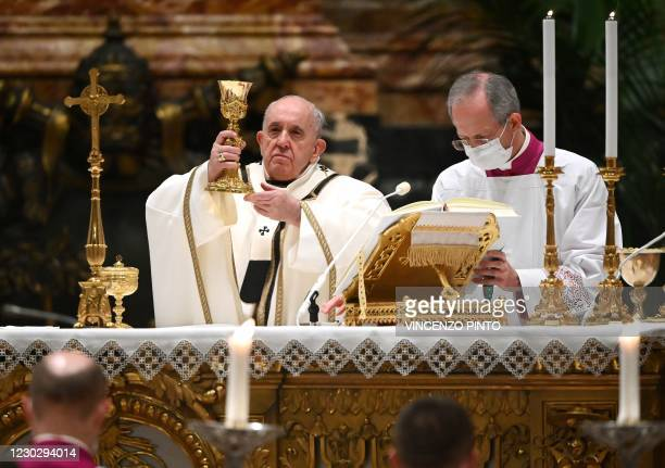 Pope Francis holds up a chalice of wine as he carries out the communion rite during a Christmas Eve mass to mark the nativity of Jesus Christ on...