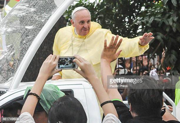 Pope Francis in his pope mobile waves to the crowd after the 'Encounter with Youth' at the University of Santo Tomas in Manila early morning on the...