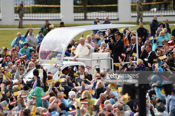 Pope Francis, in his Popemobile, waves to the crowd as he arrives to lead a Holy mass at the Shrine of the Mother of God on September 24, 2018 in...