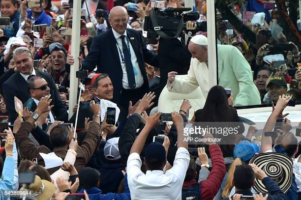 Pope Francis interacts with the crowd from the Popemobile as he arrives at the Simon Bolivar Park in Bogota to give an open air mass on September 7...