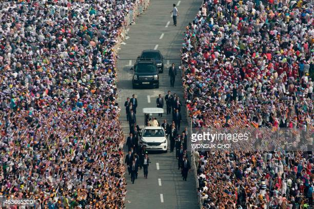 Pope Francis is driven past Catholic worshippers as he arrives to lead a mass at Gwanghwamun Square in central Seoul on August 16 2014 A tight...