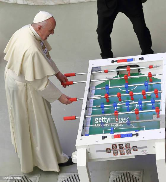 Pope Francis is entertained by playing the 'inclusive' table football gift of an association at the end of the general audience in the Paul VI Hall....