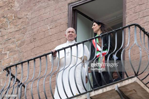 Pope Francis is flanked by Rome's mayor Virginia Raggi as he looks from a balcony overlooking the Roman forum during his visit to the Rome's city...