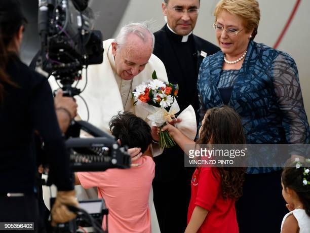 Pope Francis is given flowers by children as he is welcomed to the Arturo Merino Benitez airport by Chilean President Michelle Bachelet in Santiago...
