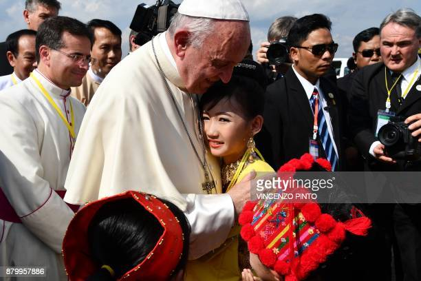 TOPSHOT Pope Francis is greeted by children in traditional clothing upon his arrival at Yangon International Airport on November 27 2017 Pope Francis...