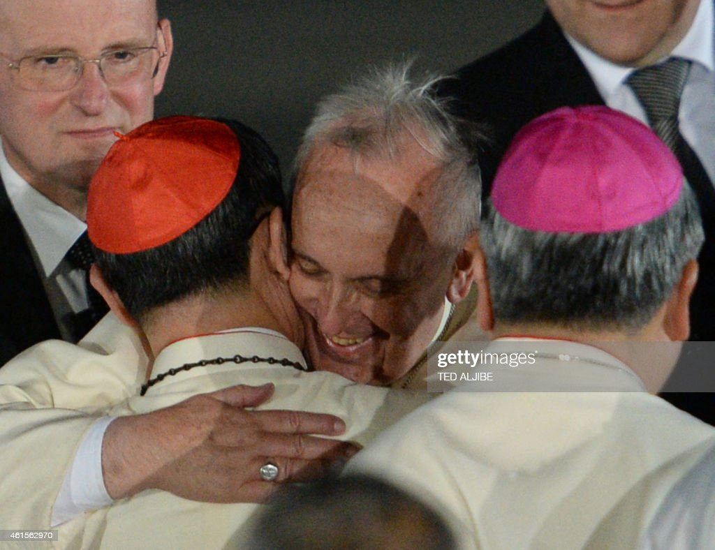 Pope Francis (C) is greeted by Philippine Cardinal Luis Tagle during a welcome ceremony shortly after arriving at a military air base in Manila on January 15, 2015. Pope Francis arrived in the Philippines on January 15 for the second leg of an Asian tour that organisers believe could see a world-record crowd turn out for a papal mass.
