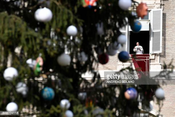 Pope Francis is pictured through the branches of a christmas tree as he addresses the crowd from the window of the apostolic palace overlooking St...