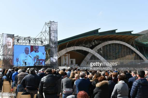 Pope Francis is seen on a giant screen during a mass in San Giovanni Rotondo on March 17 2018 as part of a pastoral visit on the 50th anniversary of...