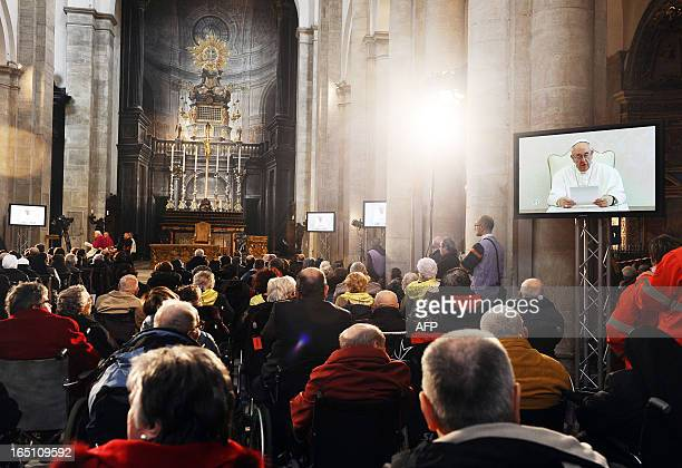 Pope Francis is seen on screens in the Turin cathedral as he provides a video message about 'The Shroud of Turin' on March 30 2013 On Holy Saturday...