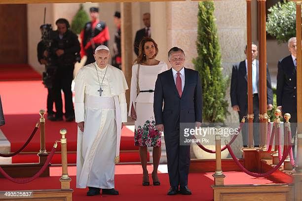 Pope Francis is welcomed by Jordan's King Abdullah II and his wife Queen Rania upon his arrival at the royal palace during his May three day visit to...