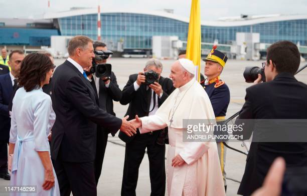 Pope Francis is welcomed by Romania's President Klaus Iohannis and his wife Carmen Iohannis after arriving at the Henri Coanda airport in Bucharest...