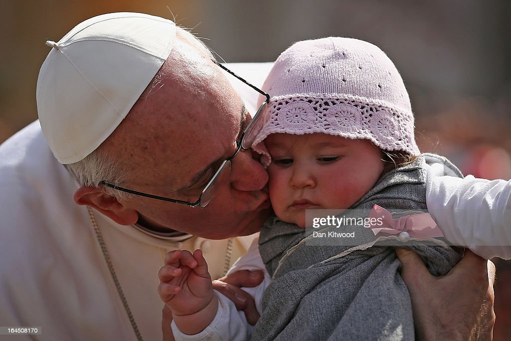 Pope Francis kisses 8-month-old Victoria Maria Marino from Sicily after delivering his blessing to the palms and to the faithful gathered in St. Peter's Square during Palm Sunday Mass on March 24, 2013 in Vatican City, Vatican. Pope Francis lead his first mass of Holy Week as pontiff by celebrating Palm Sunday in front of thousands of faithful and clergy. The pope's first holy week will also incorporate him washing the feet of prisoners in a youth detention centre in Rome next Thursday, 28th March.