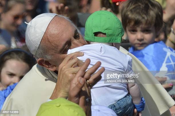 Pope Francis kisses a baby as he arrives for an audience with Catholic schools at St Peter's square on May 10 2014 at the Vatican AFP PHOTO / ANDREAS...