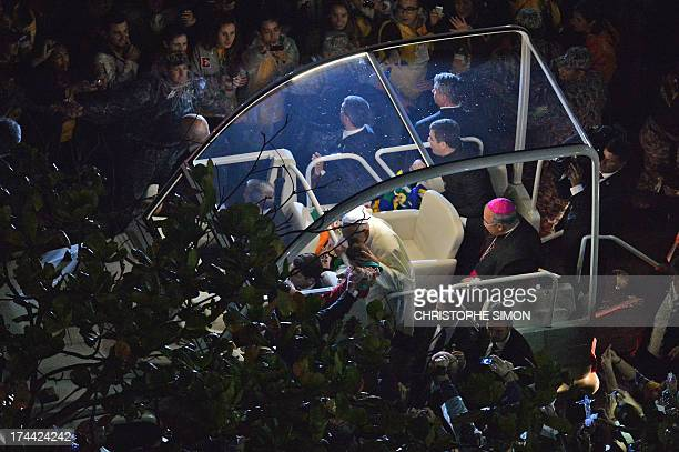 Pope Francis kisses a baby as he arrives on the popemobile at Rio de Janeiro's iconic Copacabana beachfront on July 25 2013 for his welcome to World...