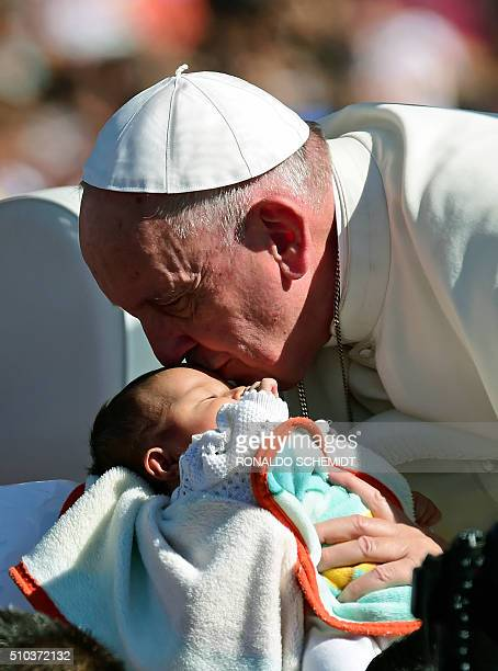 Pope Francis kisses a baby from the popemobile upon arrival in San Cristobal de las Casas in Chiapas State for his second open-air mass, on February...