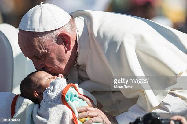 Pope Francis kisses a child as he arrives in the popemobile prior a mass with Mexican indigenous peoples on February 15 2016 in San Cristobal de las...
