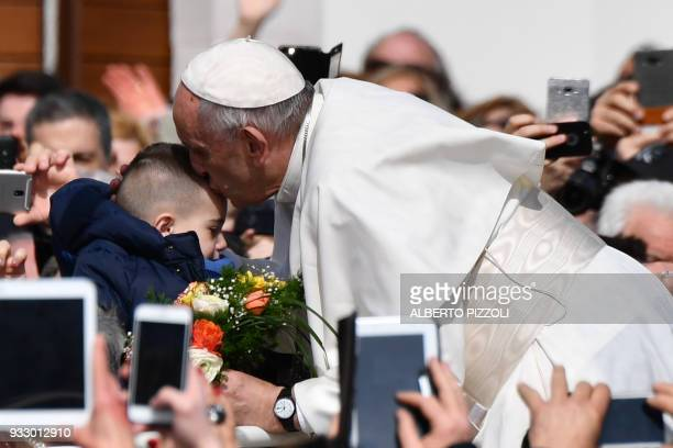 Pope Francis kisses a child in San Giovanni Rotondo on March 17 2018 during a pastoral visit on the 50th anniversary of the death of St Pio Pio was...