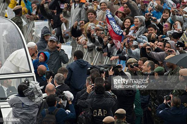 Pope Francis kisses a child upon his arrival on the popemobile at the Basilica of Our Lady of Aparecida Brazil's most revered Catholic shrine in...