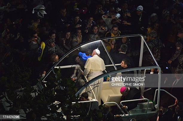 Pope Francis kisses a little boy as he arrives on the popemobile at Rio de Janeiro's iconic Copacabana beachfront on July 25 2013 for his welcome to...