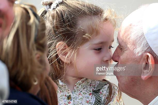 Pope Francis kisses a young girl during his weekly audience in St Peter's Square on March 19 2014 in Vatican City Vatican Pope Francis celebrated the...