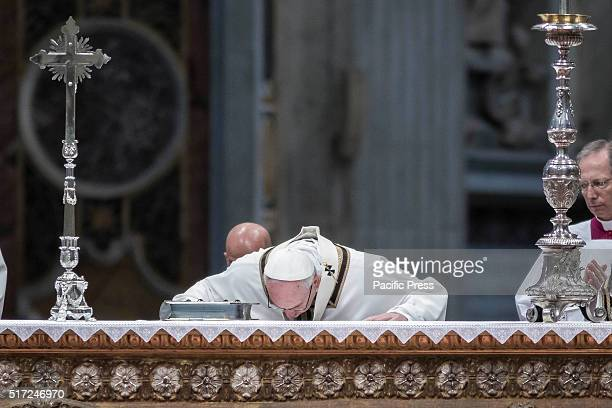 Pope Francis kisses the altar as he leads the Chrism Mass for Holy Thursday which marks the start of Easter celebrations in St. Peter's Basilica. The...