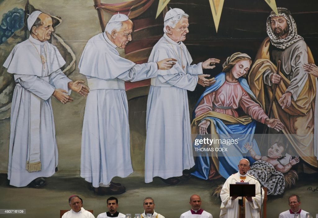Pope Francis leads an open air mass in front of a painting depicting baby Jesus at the Nativity scene covered with a Palestinian Kefiyeh, on May 25, 2014 at Manger Square in the West Bank Biblical town of Bethlehem. Pope Francis is expected to begin in Bethlehem the most sensitive part of his three-day Middle East tour aimed at forging regional peace and easing an age-old rift within Christianity.