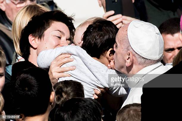 Pope Francis leans in to hug a child as he is driven across the crowd ahead of his weekly general audience in St Peter's Square at the Vatican...