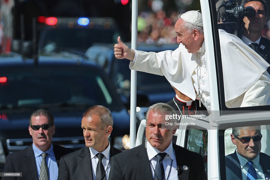 Pope Francis leans out and waves to the crowd as he rides in a popemobile along a parade route around the National Mall on September 23, 2015 in Washington, DC. Thousands of people gathered near the Ellipse to catch of glimpse of Pope Francis after he addressed an audience of 15,000 invited guests on the South Lawn of the White House during an official arrival ceremony with President Barack Obama. The Pope began his first trip to the United States at the White House followed by a visit to St. Matthew's Cathedral, and will then hold a Mass on the grounds of the Basilica of the National Shrine of the Immaculate Conception.